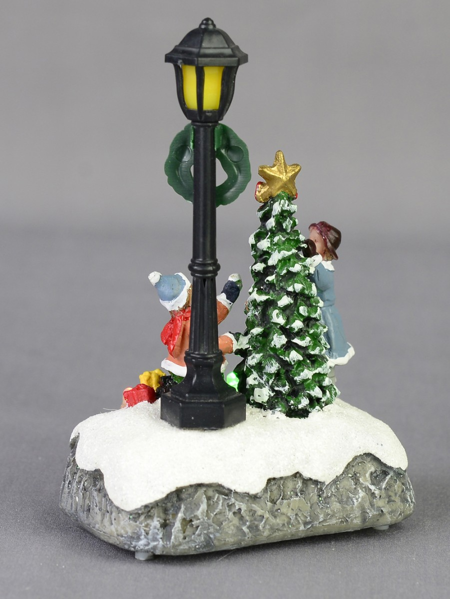 children by a christmas tree lamp post scene